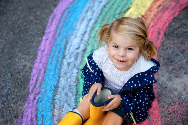 Happy little toddler girl in rubber boots with rainbow painted with colorful chalks on ground during pandemic coronavirus quarantine. Children painting rainbows along with the words Let's all be well stock photo