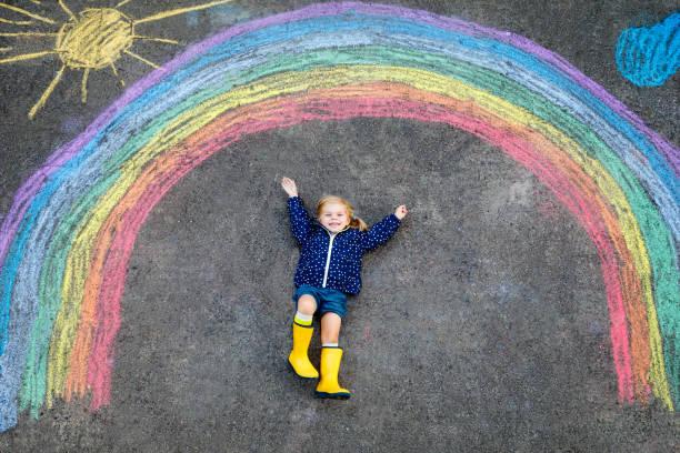 Glückliches kleines Kleinkind Mädchen in Gummistiefeln mit Regenbogensonne und Wolken mit Regen mit bunten Kreiden auf Dem boden oder Asphalt im Sommer gemalt. Nettes Kind mit Spaß. kreative Freizeit – Foto