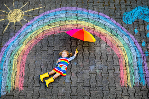 Glückliches kleines Kleinkind Mädchen in Gummistiefeln mit Regenbogensonne und Wolken mit Regen mit bunten Kreiden auf Dem boden oder Asphalt im Sommer gemalt. Nettes Kind mit Regenschirm Spaß. kreative Freizeit – Foto