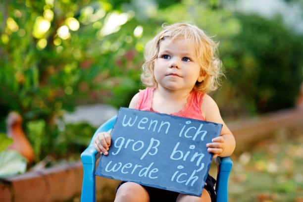 glückliche kleine kleinkind mädchen mit kreide schreibtisch in händen. gesundes entzückenden kind im freien auf schreibtisch - wenn ich groß bin ich - in deutscher sprache mit traumberuf sein wollen - abschiedswünsche stock-fotos und bilder