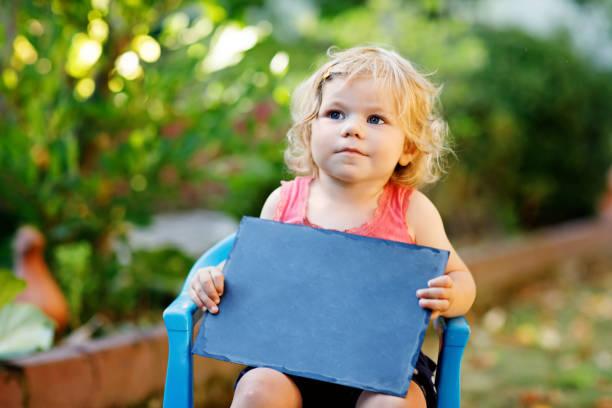 glückliche kleine kleinkind mädchen mit kreide schreibtisch in händen. gesunden entzückenden kind im freien leerer schreibtisch für exemplar durch schöne baby halten. - abschiedswünsche stock-fotos und bilder