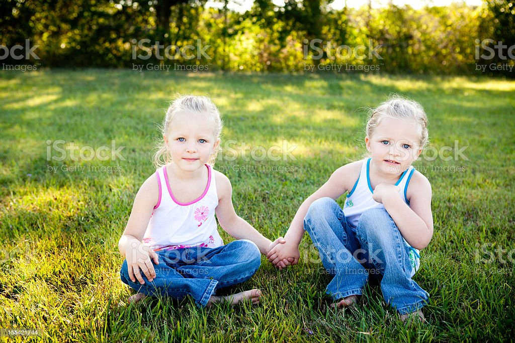 Happy Little Twin Girls Sitting Together Outside on Summer Day royalty-free stock photo
