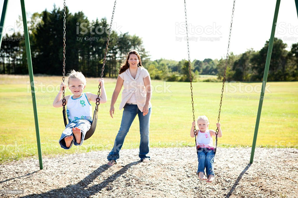 Happy Little Twin Girls Swinging Together Outside on Summer Day stock photo