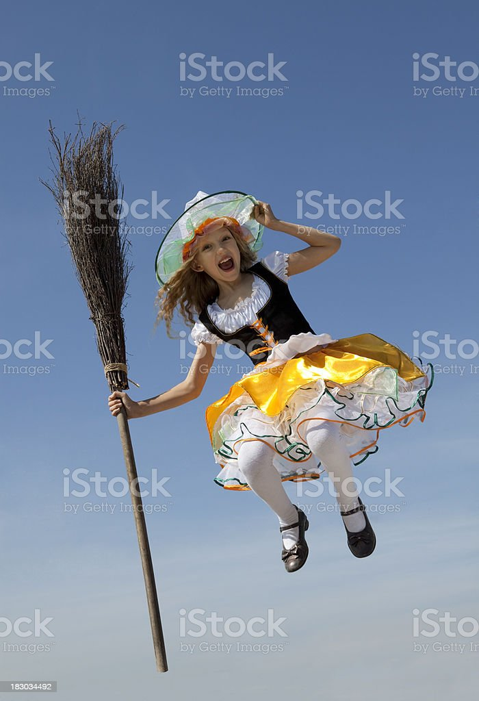 Happy Little Witch Jumping with a Broom royalty-free stock photo