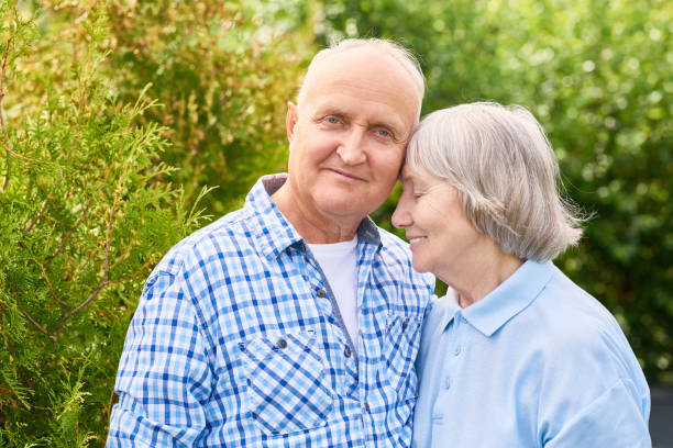 Happy  Long Marriage Portrait of loving senior couple embracing tenderly posing for camera in beautiful garden long stock pictures, royalty-free photos & images