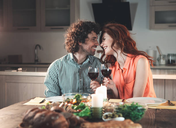 Happy lovers having dinner by candlelight stock photo