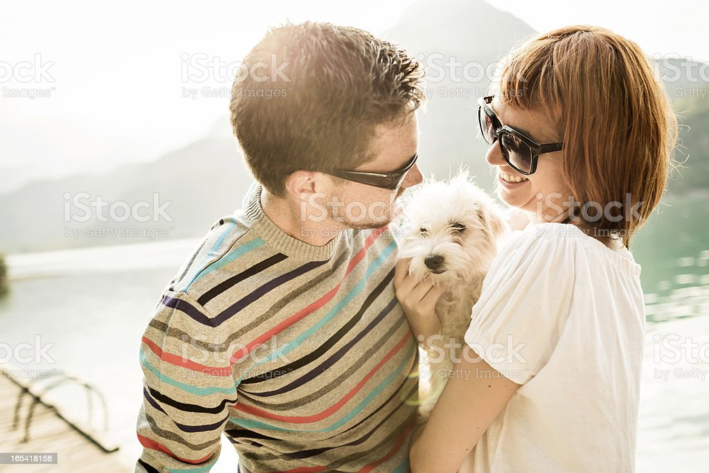 Happy Lovers with their dog during a day on Lake royalty-free stock photo