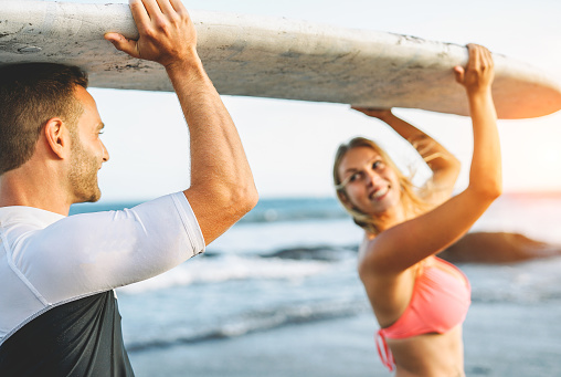 istock Happy loving couple holding a surfboard and looking each other - Friends having fun surfing during a vacation - People relationship, travel, sports lifestyle concept 1082886964