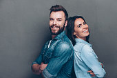 Studio shot of beautiful young couple in jeans wear standing back to back and smiling
