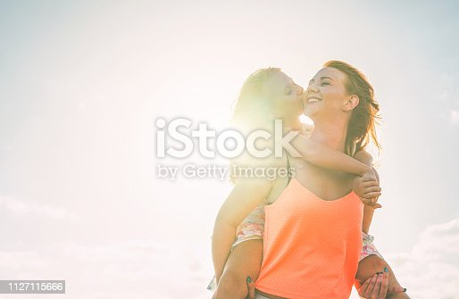 istock Happy loving family daughter kissing her mother having a tender moment on summer day - Young red hair mom carrying her kid on piggyback - Family, motherhood, childhood concept 1127115666