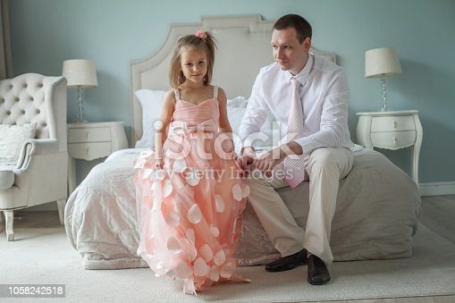 Happy loving family. Father and daughter sitting on the bed in the room