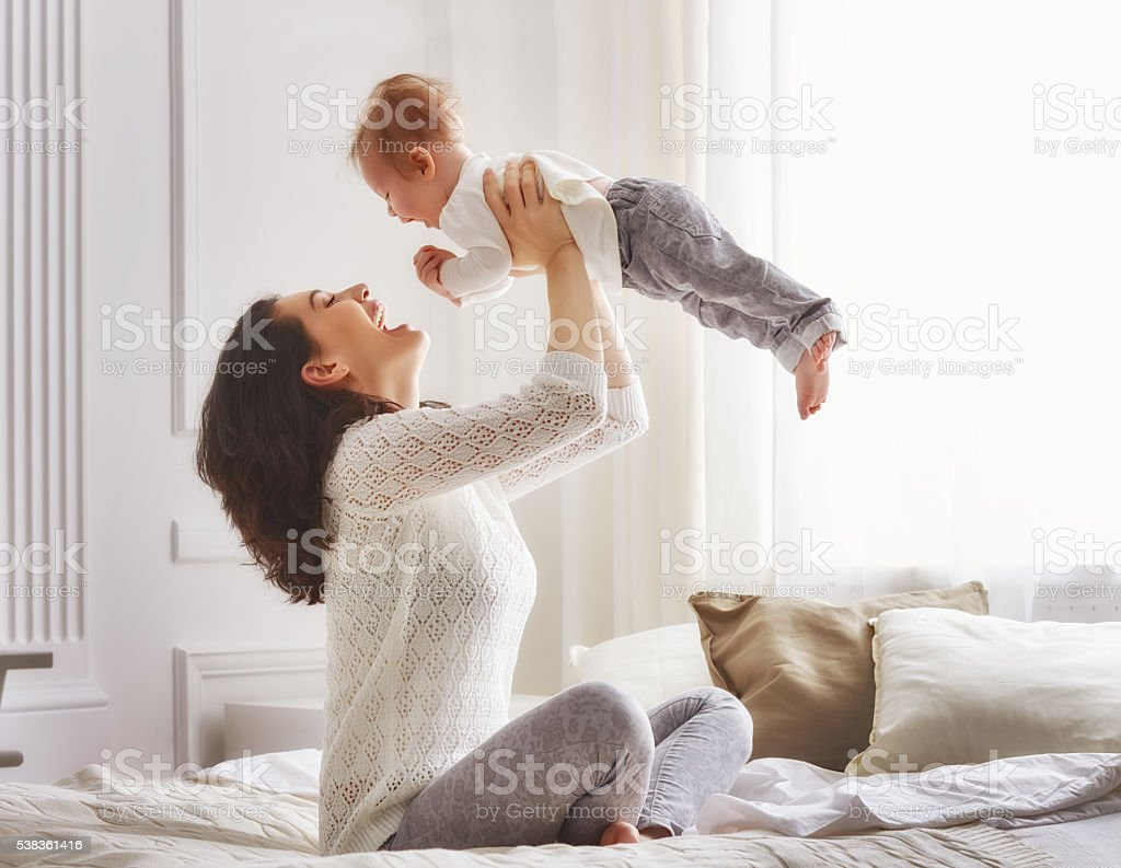 happy loving family. mother playing with her baby in the bedroom.