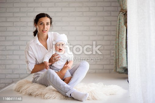638876610istockphoto Happy loving family. Young mother are playing with her baby boy 1166411145