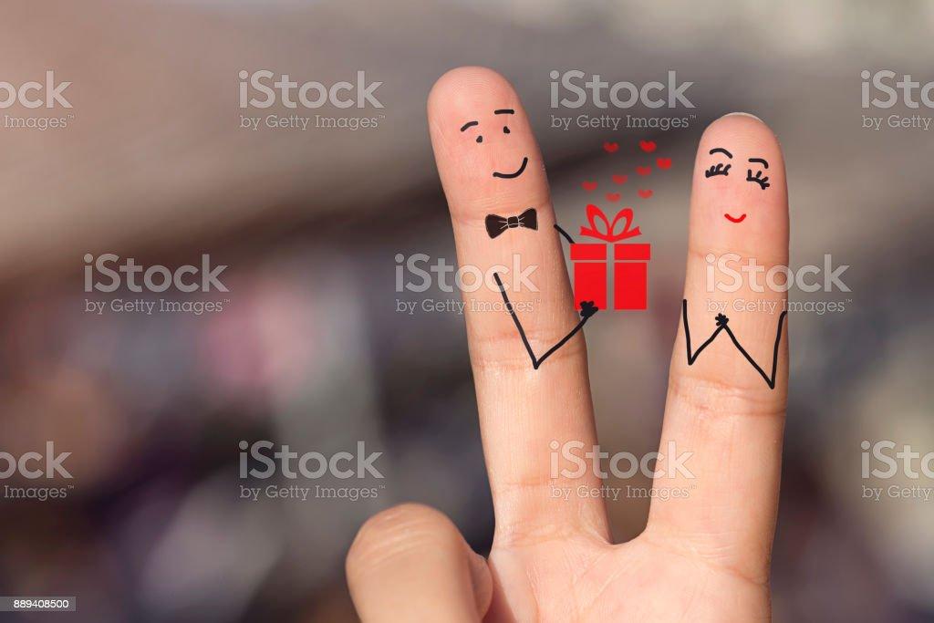 Feliz amando dedos segurando um pacote de presente do bolo - foto de acervo