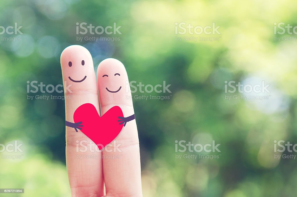 Happy loving fingers holding red heart A happy couple in love with red heart in outdoor nature, Valentines day Adult Stock Photo