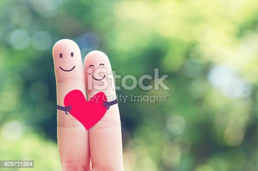 istock Happy loving fingers holding red heart 629721354