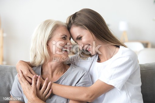 Happy loving older mature mother and grown millennial daughter laughing embracing, caring smiling young woman embracing happy senior middle aged mom having fun at home spending time together