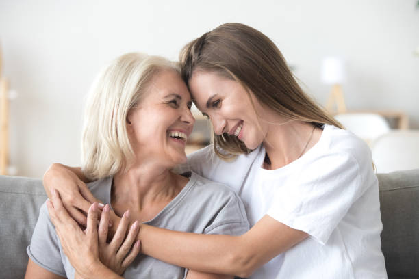 happy loving older mother and grown millennial daughter laughing embracing - só mulheres imagens e fotografias de stock