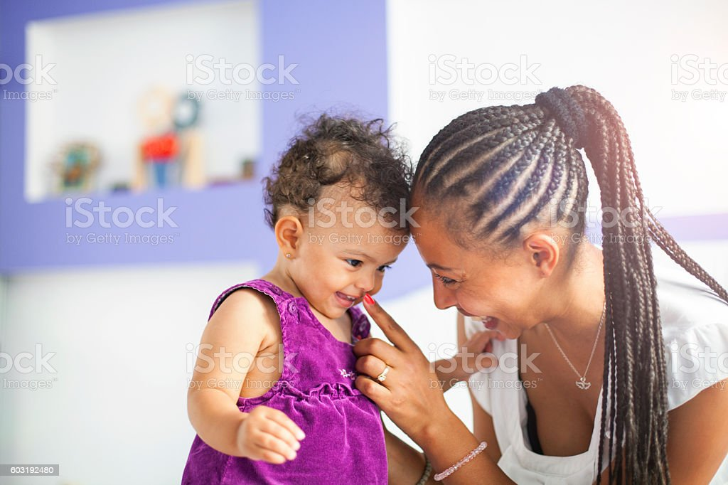 Happy lvoing young african mother holding her baby stock photo