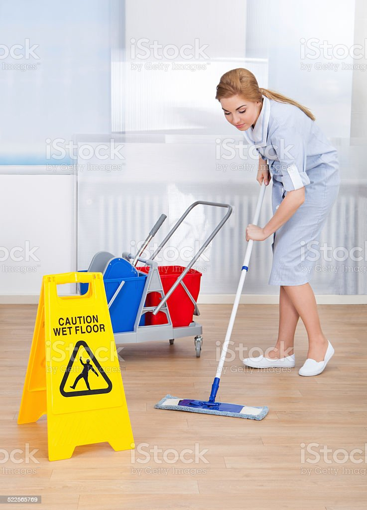 Portrait Of Young Maid Cleaning Floor With Mop