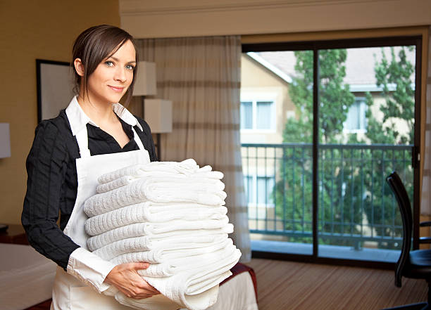 Happy maid, housekeeping with a stack of towels. Hotel room. stock photo