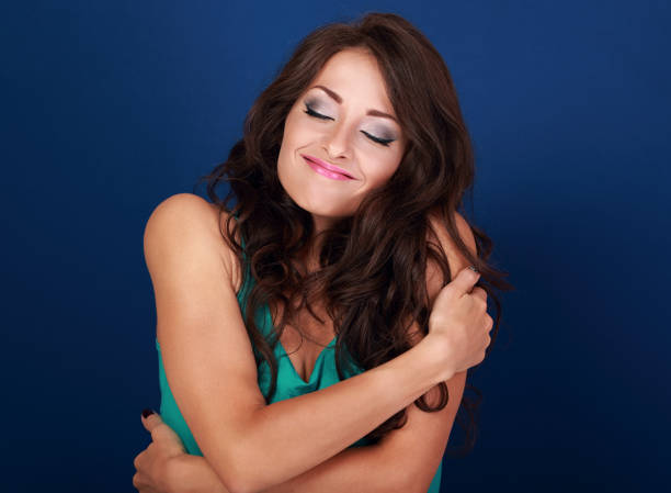 Happy makeup woman hugging herself with natural emotional enjoying face. Love concept of yourself body and face on blue background - Photo