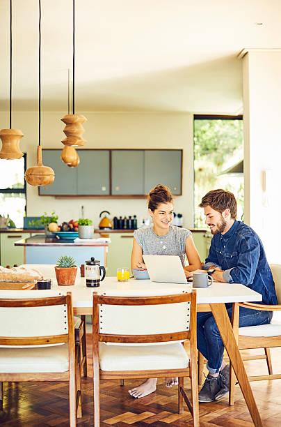 happy male and female bloggers using laptop at table - küche deko blog stock-fotos und bilder