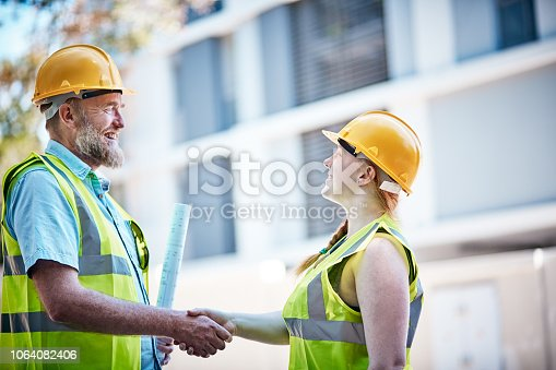 Perhaps celebrating the successful completion of a project, a man and a woman in hard hats shake hands outside a building.