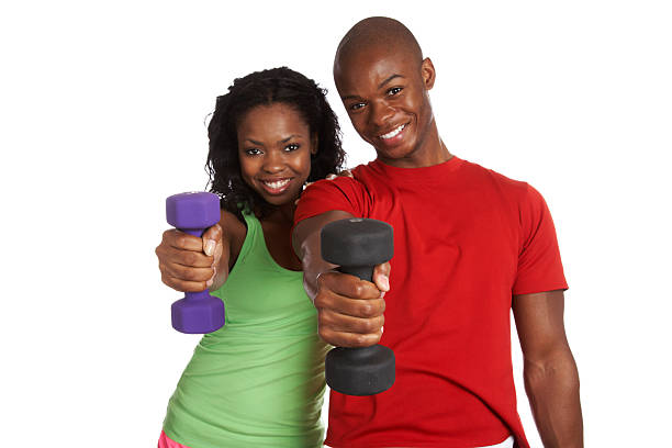 Happy male and female exercising with weights stock photo