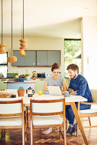 happy male and female hipsters using laptop at dining table - küche deko blog stock-fotos und bilder