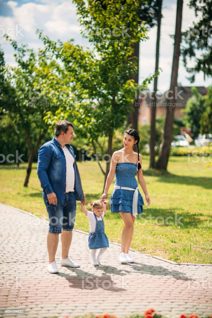 Happy male and female playing with child outside royalty-free stock photo