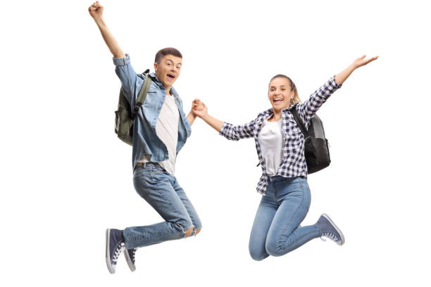 Happy male and female students jumping stock photo