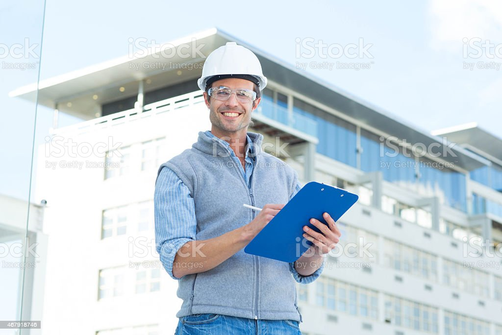 Happy male architect writing on clipboard stock photo