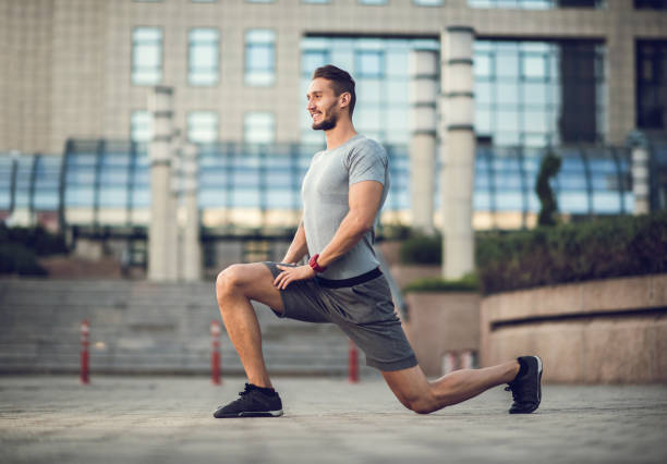 happy male athlete exercising lunges on the city street. - lunge stock photos and pictures