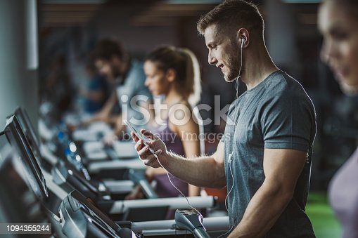 Athletic man exercising on treadmill in a gym and listening music over his cell phone.