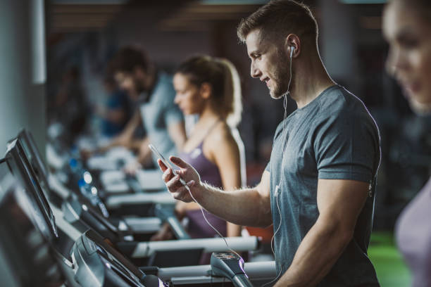 Happy male athlete listening music on treadmill in a gym. Athletic man exercising on treadmill in a gym and listening music over his cell phone. health club stock pictures, royalty-free photos & images