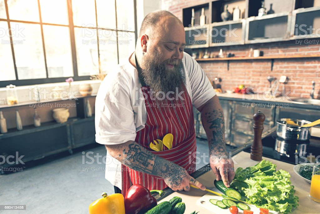 Happy male chef preparing healthy salad stock photo