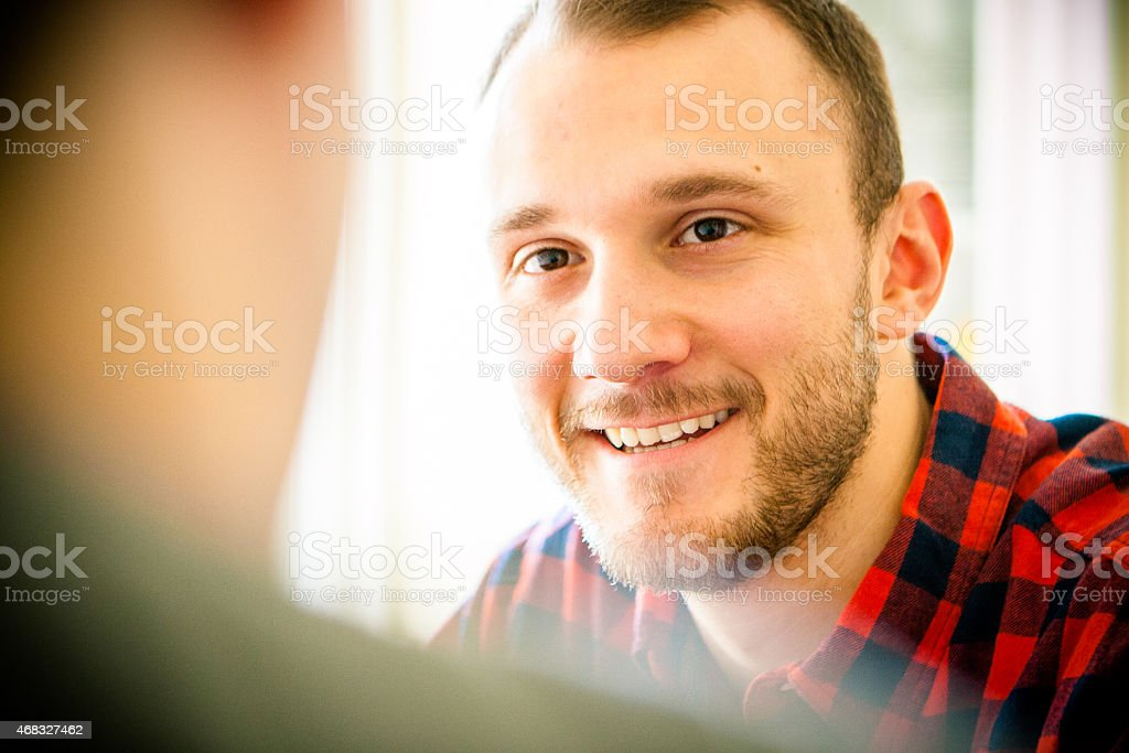 Happy male client talking to blurred rear view of life coach stock photo