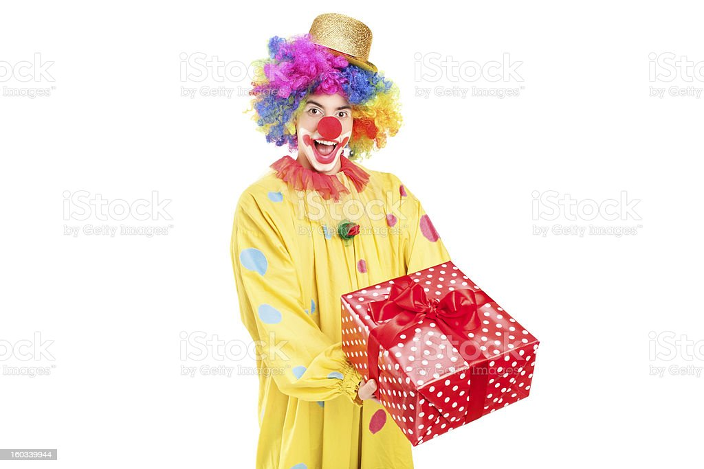 Happy male clown holding a red present royalty-free stock photo