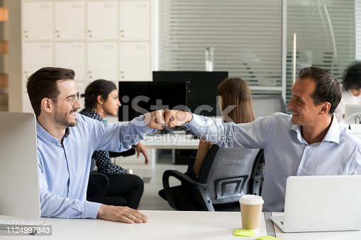 istock Happy male colleagues fist bumping sitting in office desk 1124997343