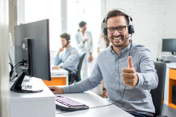 Happy male customer service operator showing thumb up in office. stock photo