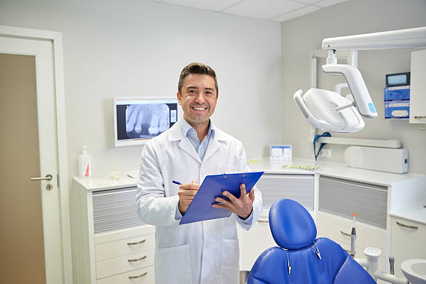 happy male dentist with clipboard at dental clinic people, medicine, stomatology and healthcare concept - happy middle aged male dentist in white coat writing to clipboard at dental clinic office male animal stock pictures, royalty-free photos & images