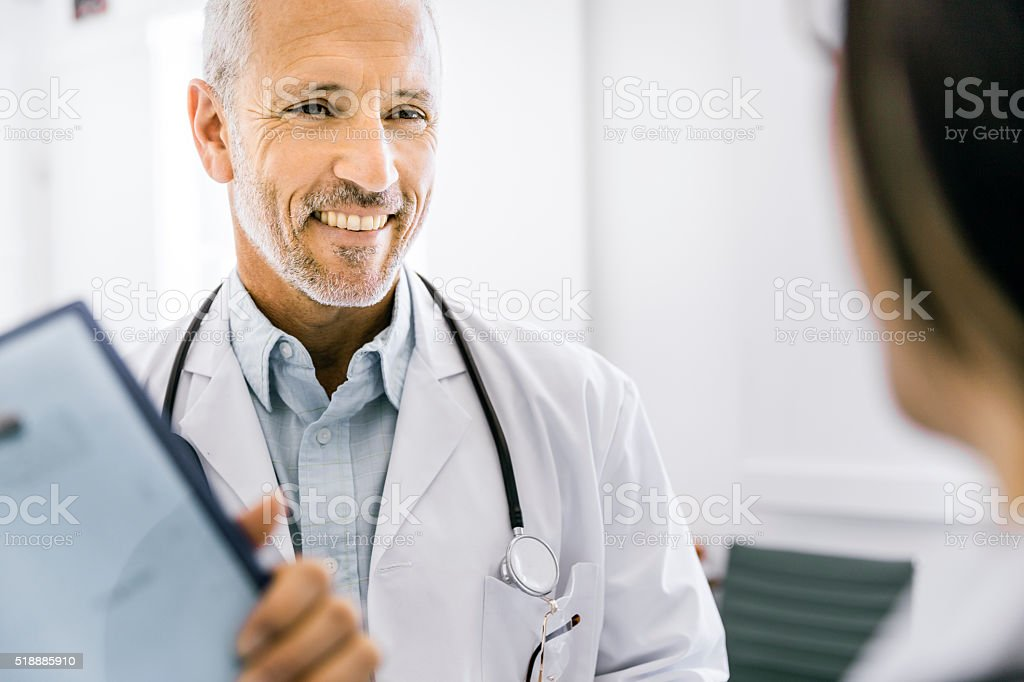 Happy male doctor discussing with female colleague stock photo