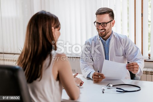 istock Happy male doctor discussing with patient at table in clinic 918196500