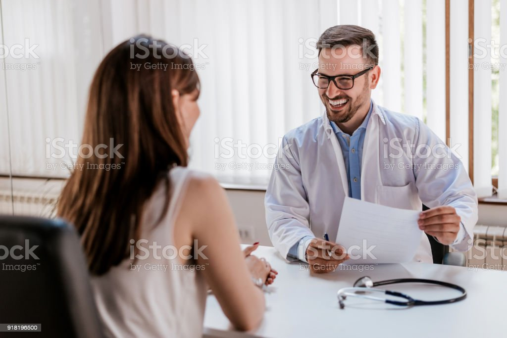 Happy male doctor discussing with patient at table in clinic stock photo