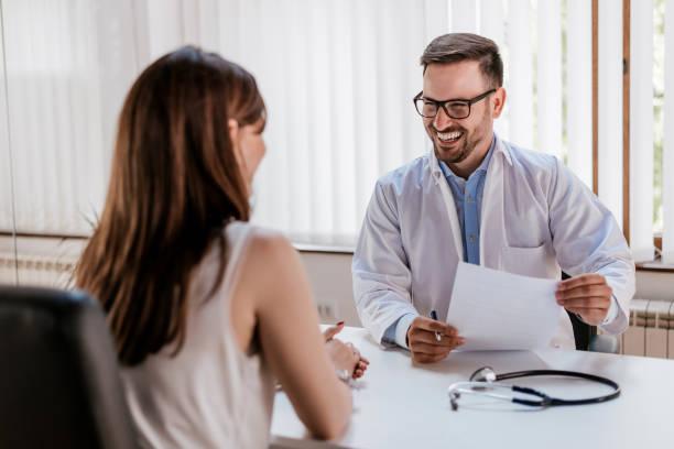 幸せの男性医師がクリニックでのテーブルに患者との議論 ストックフォト