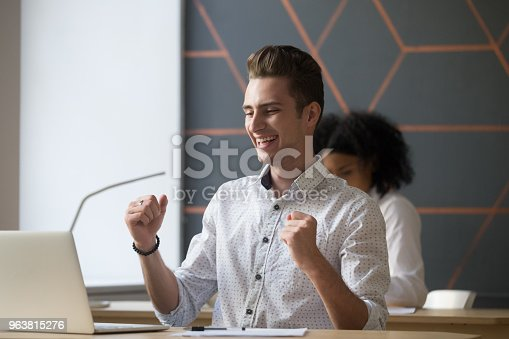 istock Happy male employee celebrating good online result looking at laptop 963815276