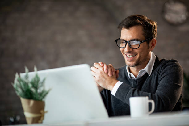 Happy male entrepreneur using laptop while working in the office. stock photo