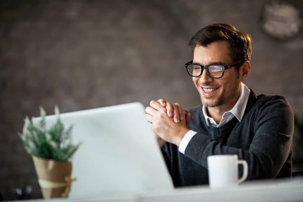 glückliche männliche unternehmer mit laptop während der arbeit im büro. - einzelner mann über 30 stock-fotos und bilder