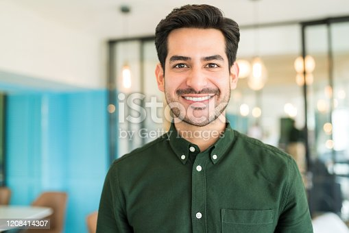 Portrait of smiling Latin businessman standing at office
